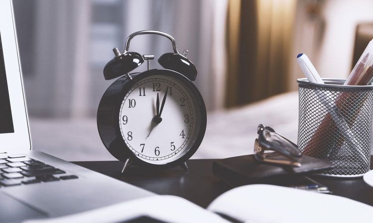"""Featured image for the """"Student Freelancers: I Don't Care What Schoolwork You're Busy With. Stick To The Deadline."""" post. It features an alarm clock on a study table."""