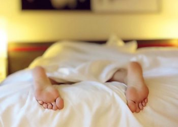 """Featured image for the """"Freelancers, Here's 7 Steps to Help You Stop Procrastinating and Actually Get Some Sh*t Done"""" post. It features feet sticking out from under some bed covers."""