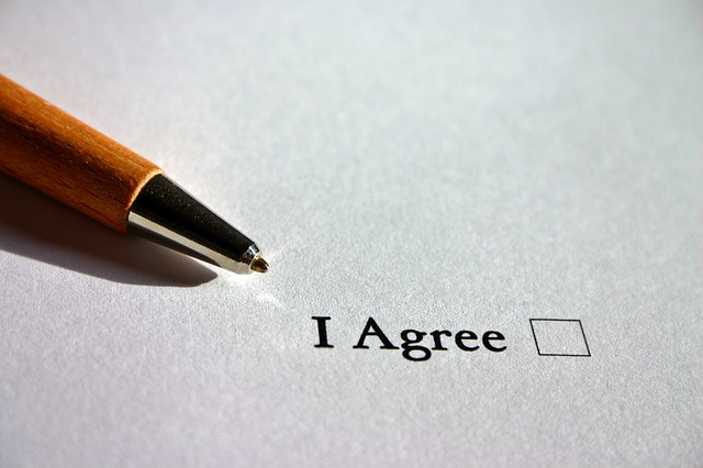"""Piece of paper with the words """"I Agree"""", and a box next to the text. Yellow ballpoint pen on the left of """"I Agree""""."""