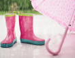 Pink rubber boots with yellow polka dots, and a light pink umbrella, on the ground on a rainy day