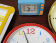 Three clocks (with yellow, red and gold frames respectively) and a blue alarm clock, on a wooden table