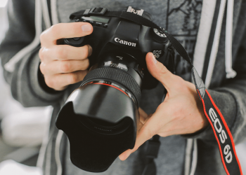 Person in grey jacket holding a Canon EOS 6D camera