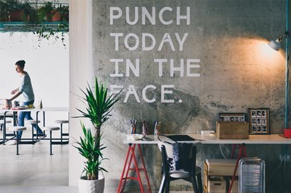 """Co-working space with """"PUNCH TODAY IN THE FACE."""" on the wall"""