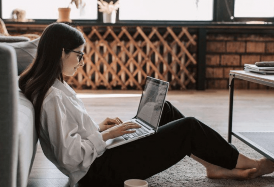 Woman using her laptop while leaning against the sofa